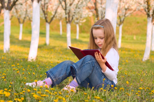 Little girl reading a book under cherry blossom tree
